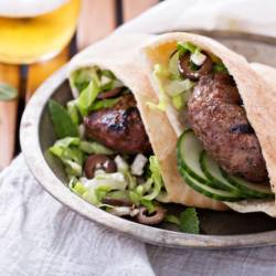 Grilled, lamb burgers in a pita with cucumbers, olives and salad