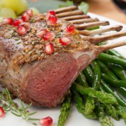 Herb crusted rack of lamb garnished with asparagus, green grapes, and pomegranates. Mini pumpkins and fresh fruits.
